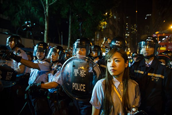 Yau Wai-ching (R) of the Youngspirations organisation, stands in front of riot police amid ongoing protests in Hong Kong on November 6, 2016. Hong Kong police used pepper spray November 6 to drive back hundreds of protesters angry at China's decision to intervene in a row over whether two pro-independence lawmakers should be barred from the city's legislature. In chaotic scenes reminiscent of mass pro-democracy protests in 2014, demonstrators charged metal fences set up by police outside China's liaison office in the semi-autonomous city. / AFP / ISAAC LAWRENCE (Photo credit should read ISAAC LAWRENCE/AFP/Getty Images)