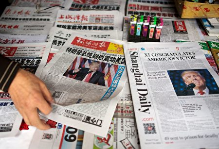 A man sorts Chinese newspapers featuring Donald Trump's victory in the US presidential elections on their front pages in Shanghai on November 10, 2016. The American public on November 9 voted for the Republican candidate Donald Trump to be the 45th President of the United States. / AFP / JOHANNES EISELE (Photo credit should read JOHANNES EISELE/AFP/Getty Images)