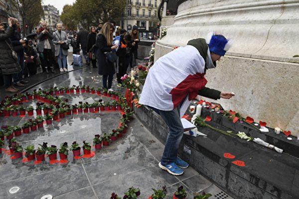 2016年11月13日,法國巴黎恐怖襲擊一周年,法國全國舉行全天紀念活動。圖為一名男子在紀念碑前點燃蠟燭,憑弔去年此時去世的130名罹難者。(ALAIN JOCARD/AFP/Getty Images)