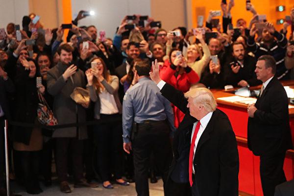 美國候任總統特朗普,美東時間22日下午約1時許到《紐約時報》總部,與發行人蘇茲貝格和其他資深記者會面。圖為特朗普會談結束後和紐時總部大廳記者及人群揮手。(Spencer Platt/Getty Images)