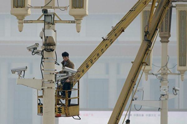 一名男子於2013年10月31日在北京天安門廣場檢查監視鏡頭。(Ed Jones/AFP/Getty Images)