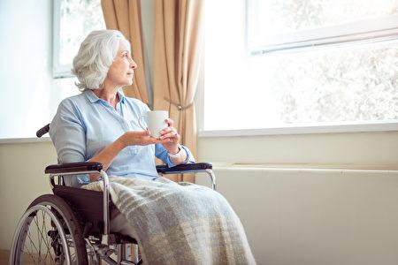 高年孤独的女人坐在轮椅上,手拿着茶看着窗外。