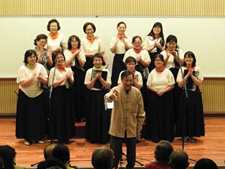 """旅奥音乐家谢英杰老师(前立者),在""""平安喜乐合唱音乐会""""中,宣布将指挥棒传承给团长萧丽华。(蔡上海/大纪元)"""