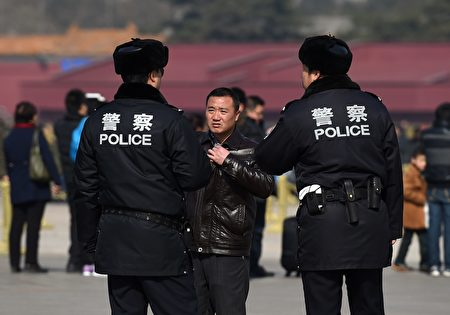 """Chinese police question a man (C) in Tiananmen Square, next to the Great Hall of the People, the venue for upcoming meetings of China's legislature in Beijing on March 2, 2015. China's Communist Party-controlled legislature, the National People's Congress (NPC), gathers in the capital this week with the """"rule of law"""" high on the agenda. AFP PHOTO / Greg BAKER (Photo credit should read GREG BAKER/AFP/Getty Images)"""