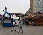 柏林波茨坦广场上的圣诞市场关闭,只有寥寥无几的人穿行而过。(周仁/大纪元)