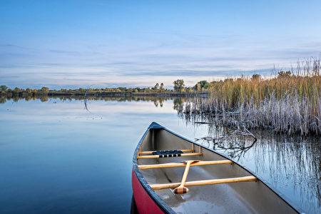 dusk over calm lake with a canoe