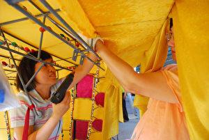兩人在篷裡,一個兩手緊抓篷布,一人圓睜眼睛,拿著電動機將篷布釘上。(圖/王金丁)