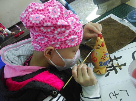 冈山国小罹病学童视力距离只有5~10公分,却以无比专注的神情彩绘她的作品,并祝福大家新年充满欢乐喜悦。冈山国小罹病学童视力距离只有5~10公分,却以无比专注的神情彩绘她的作品,并祝福大家新年充满欢乐喜悦。(林晋如老师提供)