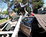 圖為2014年8月24日納帕發生了6.1級地震後,居民從倒塌的車棚中取出了車子中的兒童座椅。地震造成80多人受傷,建築設施損壞及斷電。(read Josh Edelson/AFP/Getty Images)