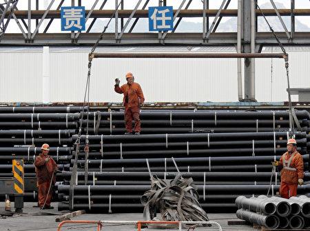中国钢铁业劳工正在准备将钢管装载到卡车上。(STR/AFP/Getty Images)