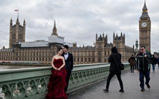 真人演示,美麗凍人。英鎊貶值,中國遊客來英國拍攝婚紗照,不小心趕上英國最近降溫,身邊的行人都穿著厚厚的棉服,婚紗總不能也變成羽絨的吧。新郎還好說,至少西裝有袖子、不露肩,可憐的新娘想必已經瑟瑟發抖了吧。 (Photo by Chris J Ratcliffe/Getty Images)