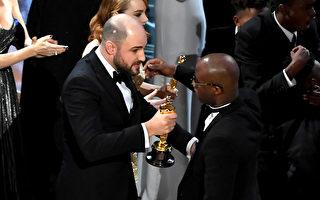 在《愛樂之城》(La La Land,台譯:樂來樂愛你)被宣布獲得最佳影片後,劇情大逆轉,《月光男孩》(Moonlight)才是大獎得主。圖為《愛樂之城》製片人向《月》片導演兼編劇交接獎杯。 (Kevin Winter/Getty Images)
