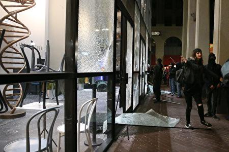 Chase銀行遭到抗議者的破壞,一女子禁止人們拍照。(Elijah Nouvelage/Getty Images)
