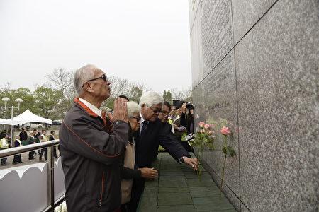 縣長李進勇攙扶著受難者家屬代表,獻上洋桔梗來悼念受難者英魂。(雲林縣府提供)
