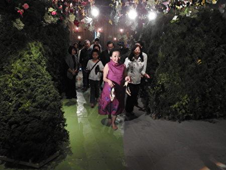 在2017年世界搏茶會中,嘉義縣長張花冠脫鞋體驗「水影主題館」的情境。(蔡上海/大紀元)
