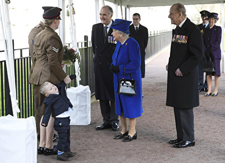 """Two year old Alfie Lun is held by his mother as Britain's Queen Elizabeth II arrives to unveil The Iraq and Afghanistan memorial at Victoria Embankment Gardens in central London on March 9, 2017. The preceding """"Service of Dedication"""" honoured the service and duty of both the UK Armed Forces and civilians in the Gulf region, Iraq and Afghanistan, and those who supported them back home, from 1990-2015 / AFP PHOTO / POOL / Toby Melville (Photo credit should read TOBY MELVILLE/AFP/Getty Images)"""