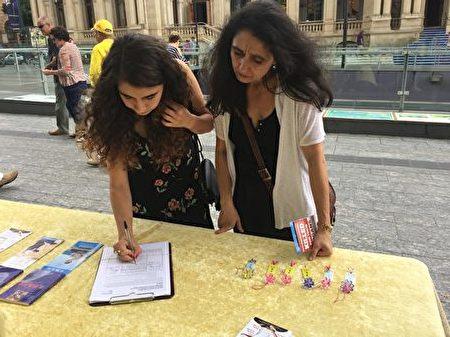 布里斯本民眾在呼籲聯合國幫助制止迫害法輪功的徵簽表格上簽名。(夏玲/大紀元)