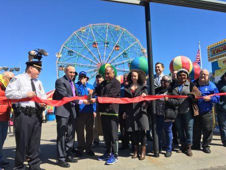 """上午11点左右,康尼岛市议员崔马克(右二)和游乐园业主等在""""迪诺奇迹公园""""门口举行了剪裁仪式。"""