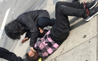 被搶的老闆娘被劫匪打倒在地,路人協助報警。 (目擊者提供)