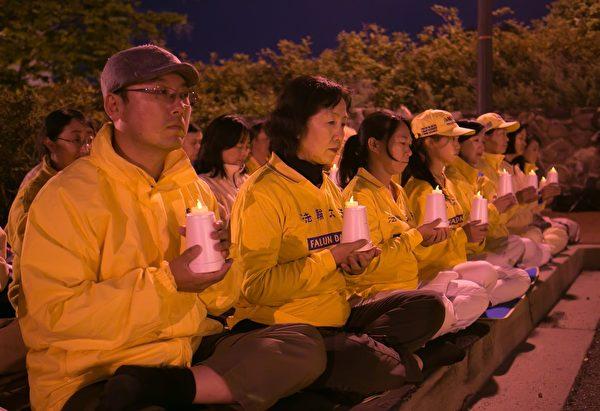 4月23日傍晚,华府法轮功学员点燃烛光,哀悼被中共迫害致死的法轮功学员。(李莎/大纪元)