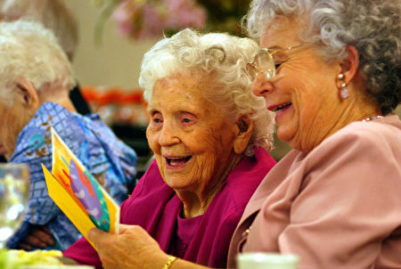 LOS ANGELES, CA - AUGUST 16: Mamie Underhill (L), 104, and her daughter Leita Chapman laugh while reading a birthday card for Mamie during a birthday celebration for five women residents at the Solheim Lutheran Home who are 100-years-old or more August 16, 2002 in Los Angeles, California. Mamie turns 105 on September 19. (Photo by David McNew/Getty Images)