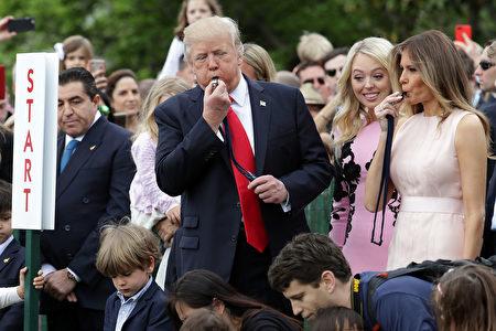 總統吹響開場口哨。川普夫婦跟兒子巴倫一起觀看了滾彩蛋,並簽署了給軍隊的慰問卡。 (Chip Somodevilla/Getty Images)