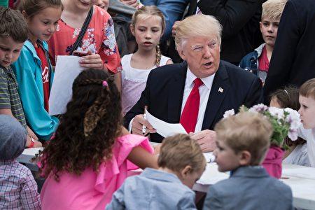川普夫婦跟兒子巴倫一起觀看了滾彩蛋,並簽署了給軍隊的慰問卡。(BRENDAN SMIALOWSKI/AFP/Getty Images)