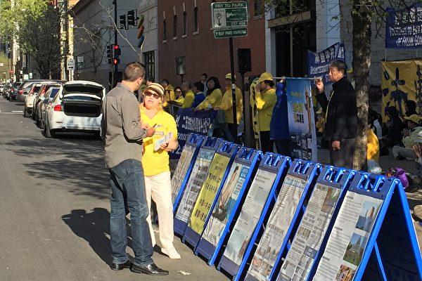 """2017年4月23日,法轮功学员在芝加哥中领馆前举行集会,纪念""""四‧二五""""和平上访18周年。图为路人向法轮功学员了解真相。(Lisa Zhu/大纪元)"""