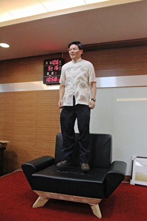 鍾昱緯董事長親在環保無木強固型組合沙發蹦跳,獲金奬。(許享富/大紀元)