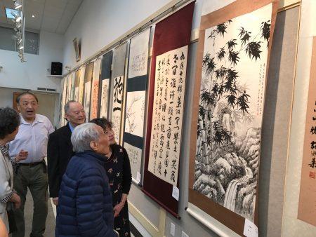 百岁书画家丁兆麟(前)在观赏美国华人书画协会的书画展。