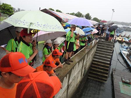 嘉義縣第34屆龍舟競賽雖然冒雨登場,但由縣議會秘書長黃尚文(站堤防上者)帶領的議會啦啦隊卻仍然熱情加油不已。(蔡上海/大紀元)