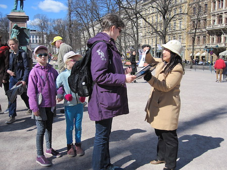 5月6日,芬兰法轮功学员在赫尔辛基的海滨公园,向人们介绍法轮功,并讲述迫害真相。(李乐/大纪元)