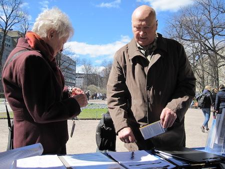 法轮功学员向一位前来签名的芬兰人(图右)讲述迫害真相。(李乐/大纪元)