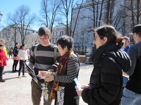 法轮功学员进行反迫害征签,一位年轻人(图左)拿着签名表仔细阅读。(李乐/大纪元)