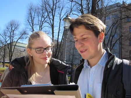 一对年轻人拿着签名表仔细阅读。(李乐/大纪元)