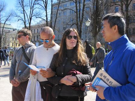 法轮功学员(右一)讲真相,民众仔细聆听。(李乐/大纪元)