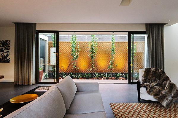 (原本狭窄的外部空间,通过有纹理的金属板、植物及灯光的处理,为室内空间创造了独特的背景。Whyte Gardens提供)