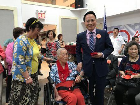 駐紐約台北經文處副處長陳豐裕向八十歲以上耆老派紅包。