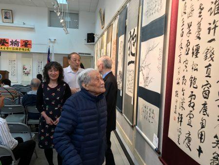 会长王懋轩陪同103岁书画家丁兆麟观赏美国华人书画艺术家协会的书画展。