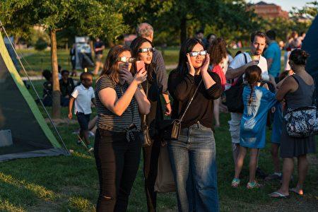 游客通过活动上提供的免费太阳镜观察太阳。(石青云/大纪元)