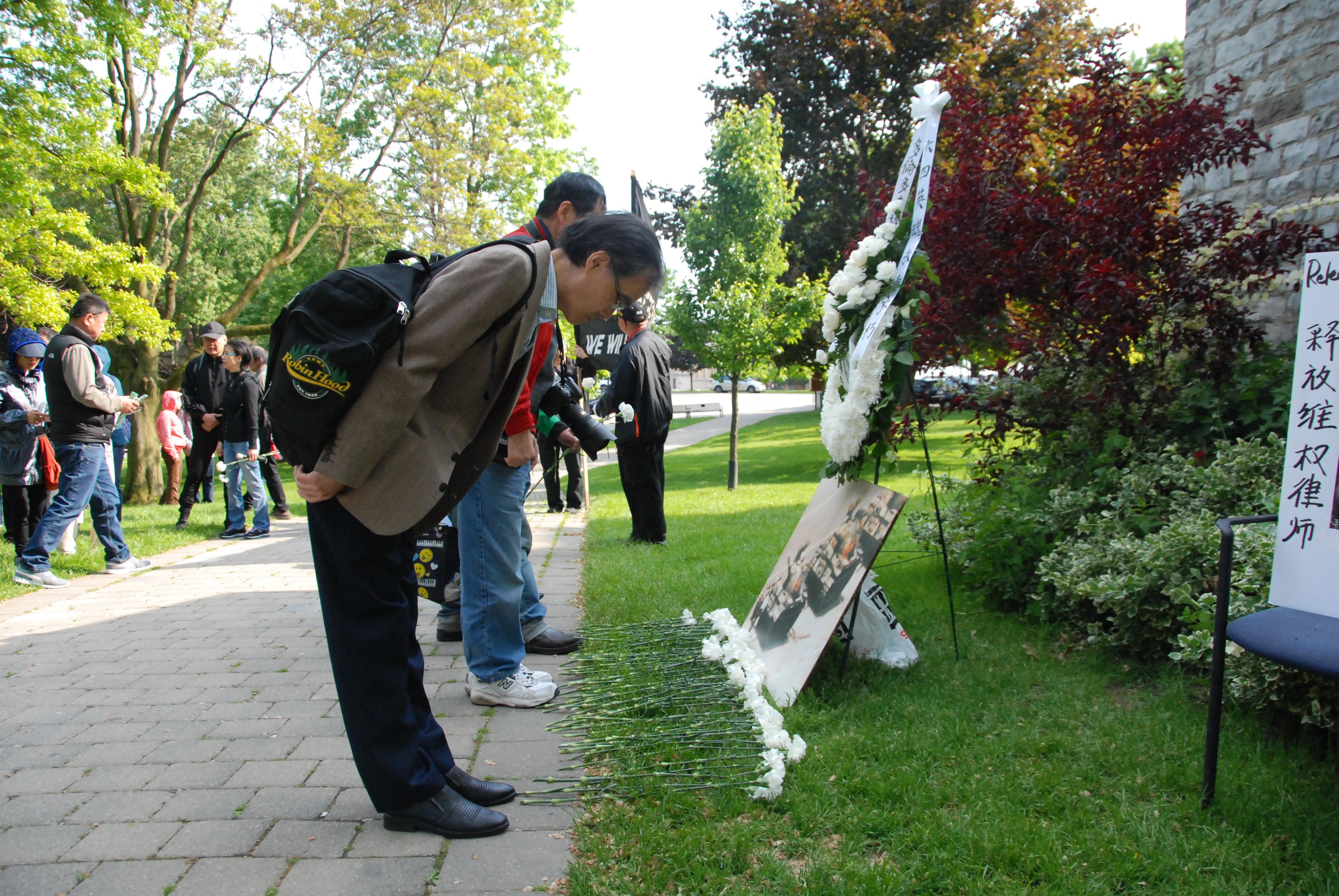 """民众在多伦多大学""""六四""""纪念碑前献花表达心声。(伊铃/大纪元)"""