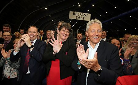 Democratic Unionist Party (DUP) deputy Nigel Dodds (L), leader Arlene Foster (C) and Former Democratic Unionist Party (DUP) Leader, Peter Robinson (R) celebrate at the counting centre in Belfast, Northern Ireland, early in the morning of June 9, 2017, hours after the polls closed in Britain's general election. Prime Minister Theresa May is poised to win Britain's snap election but lose her parliamentary majority, a shock exit poll suggested on June 8, in what would be a major blow for her leadership as Brexit talks loom. The Conservatives were set to win 314 seats, followed by Labour on 266, the Scottish National Party on 34 and the Liberal Democrats on 14, the poll for the BBC, Sky and ITV showed. / AFP PHOTO / Paul FAITH (Photo credit should read PAUL FAITH/AFP/Getty Images)