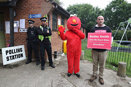 MAIDENHEAD, ENGLAND - JUNE 08: Candidate Bobby Smith arrives with Elmo as Police wait outside the polling station where Conservative Party leader Theresa May is expected to vote on June 8, 2017 in Maidenhead, England. Polling stations have opened as the nation votes to decide the next UK government in a general election. (Photo by Matt Cardy/Getty Images)