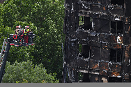 Emergency workers inspect the remains of Grenfell Tower, a residential tower block in west London which was gutted by fire, on June 16, 2017. Dozens of people are feared dead in the London tower block fire as emergency workers continued searching for bodies in the high-rise on Friday, warning they may never be able to identify some of the victims. / AFP PHOTO / Chris J Ratcliffe (Photo credit should read CHRIS J RATCLIFFE/AFP/Getty Images)