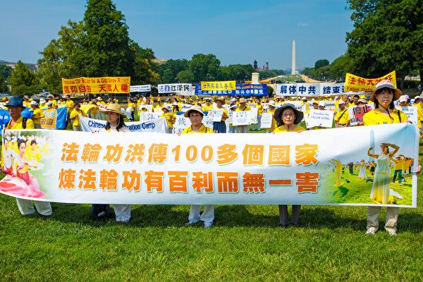 """法轮功学员手举横幅""""法轮功洪传100多个国家,炼法轮功有百利而无一害。""""(MARK ZOU/大纪元)"""