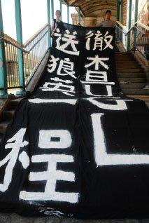 6月30日,習近平未如預料到中聯辦。有示威團體在中聯辦附近天橋鋪出要求習近平當局徹查梁振英UGL涉貪事件的橫幅。(大紀元資料圖片)
