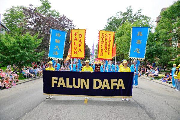 「FALUN DAFA」的橫幅和旗子走在法輪功遊行隊伍的最前面。(David Yang/大紀元)