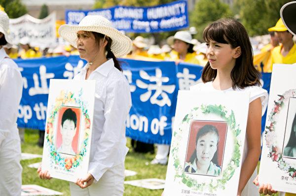 法轮功学员手捧照片,悼念被迫害致死的中国法轮功学员。(李莎/大纪元)