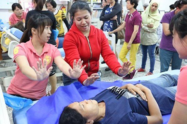 羅東博愛醫院居家護理所護理師傳授外籍照顧者學習翻身擺位的技巧。(羅東博愛醫院提供)