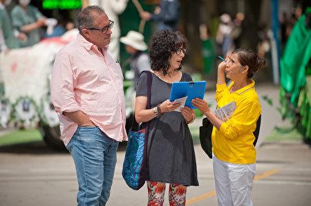 """图说:2017年7月16日,温哥华""""七二零""""反迫害集会上,法轮功学员向市民、游客讲真相,很多民众了解真相后签字支持。(摄影:大宇/大纪元)"""